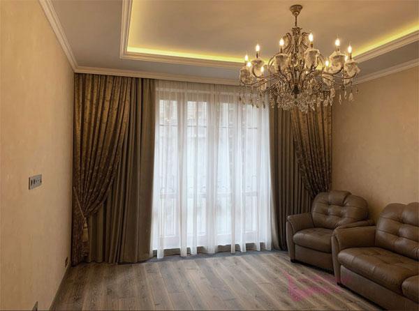 Шторы в гостиную ШГ0102. Комбинированные тройные, золотистые шторы с узором в классическом стиле, собранные в складки шнуром с кистями. Второе полотно прямое, коричневое. Дополнение - белый, полупрозрачный тюль.